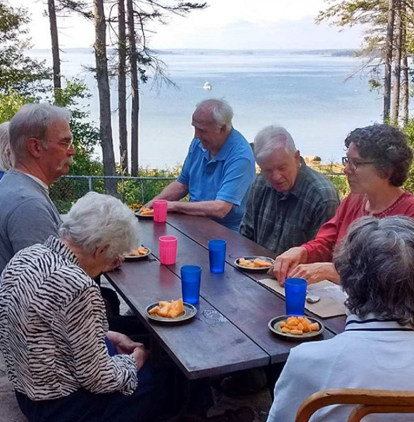 Residents enjoy meals on the patio, overlooking Casco bay.